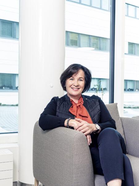 Tarja Tikkanen KPY nainen istua hymy hymyillä iloinen aulatila ala-aula kokoustila puheenjohtaja